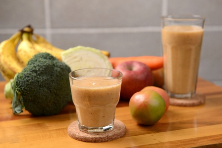 Smoothie made of grinded apples and carrots in glass