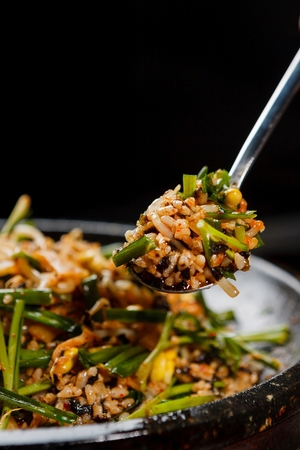Spoon scooping up stir-fried rice with lots of chives and dried seaweed, made on iron plate