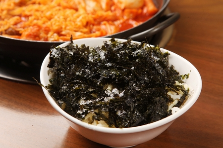 Rice with lots of dried seaweed powder on white plate