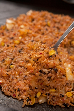 Spoon scooping up stir-fried kimchi rice with kimchi and bean sprouts, made on iron plate