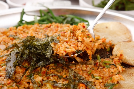 Spoon scooping up stir-fried kimchi rice with sprinkled dried seaweed on plate