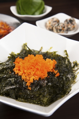Rice balls with dried seaweed powders and flying fish roe, on white rectangular plate