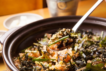 Spoon scooping up stir-fried rice with chives and dried seaweed powder, on china plate