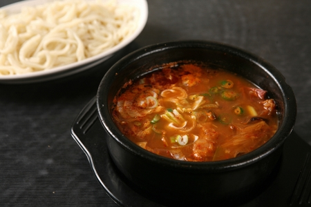 Hot spicy meat stew in pot, with chopped noodles
