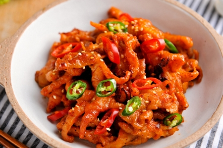 Spicy boneless chicken feet with chili on china plate Banco de Imagens