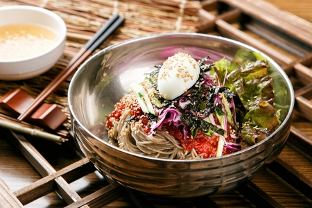 Buckwheat noodles with egg, sprouts and dried seaweed powder in bowl