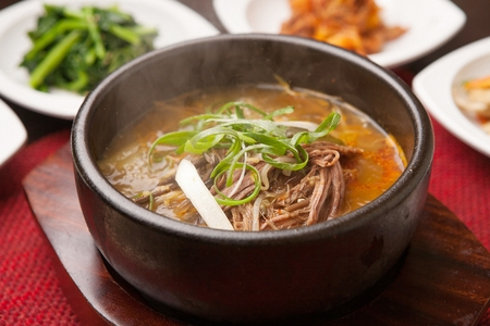 Rice soup with beef, in pot with side dishes
