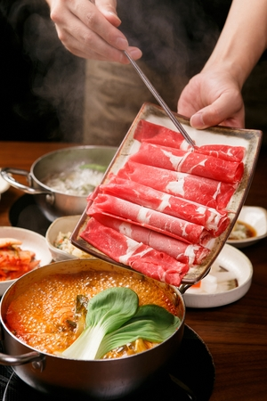 Shabu-shabu broth in pot, and meat on plate