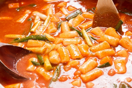Spicy Rice Cake with spring onion served on pan with spatula and ladle 스톡 콘텐츠 - 117511108