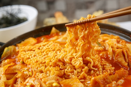 Spicy Rice Cake with ramen noodles with bean sprouts served on pan with chopsticks