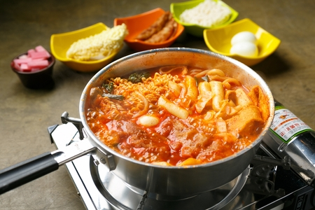 Spicy Rice Cake with ramen noodles served in pot on burner and spicy rice cake ingredients served in bowl Foto de archivo