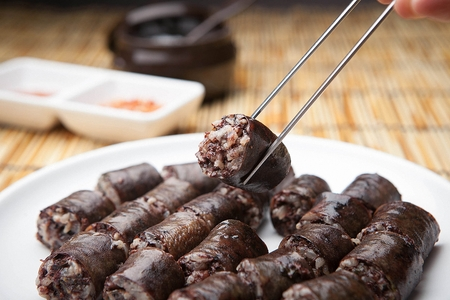 Korean Blood Sausage served on plate on bamboo shoot with chopstick