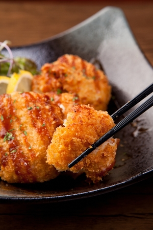 Croquette with sauce on top served on plate with chopstick Stock Photo