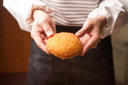 Chefs Hand grabbing Croquette