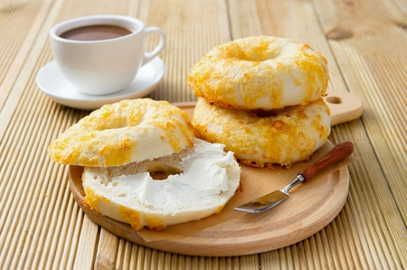 Cheese Bagel with cream put on served on wooden plate with coffee