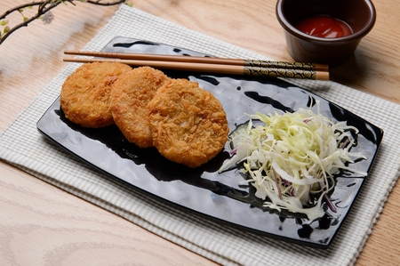 Croquette, with sauce and Cabbage salad served on plate with chopstick Stock Photo