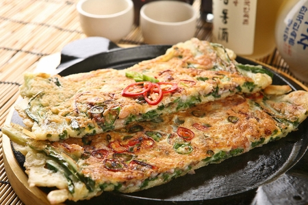 Spring Onion Korean Pancake with red and green chili pepper inside served on wooden grill plate