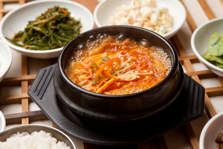 Kimchi stew with mushrooms and red chili peppers inside served in Korean pot with side dishes 免版税图像