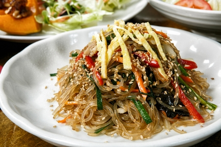 Stirfried glass noodles with carrot, pepper, spinach, and egg garnish inside served on plate