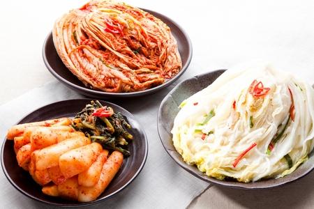 Cabbage Kimchi, radish kimchi, and white kimchi served on plate