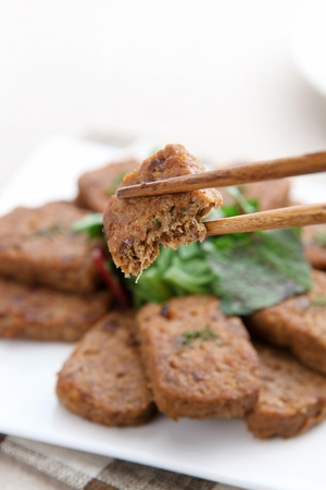 Grilled short rib patties with german turnip and parilla leaves on top served on plate with chopsticks Zdjęcie Seryjne