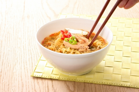 Ramen with mushrooms, chicken, green and red chili peppers on top served in bowl with chopsticks 版權商用圖片