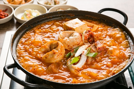 Kimchi stew with dumplings and tofu inside served in pot on burner with side dishes