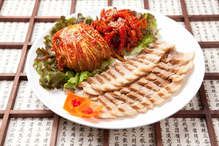Korean cuisine Suyuk, boiled pork slices with sesame seeds, cabbage kimchi and spicy dried radish salad
