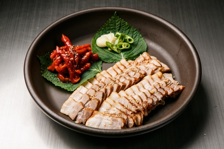 Korean cuisine Suyuk, boiled pork slices, thinly sliced garlic and green pepper and spicy dried radish in porcelain bowl