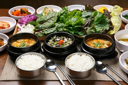 Korean cuisine Ureong Doenjang, soy bean paste  with sea squirt topped with spring onions and Doeunjang Jjigae, soy bean paste stew in Ttukbaegi, earthen pot with side dish, wrapping greens and rice Stock Photo