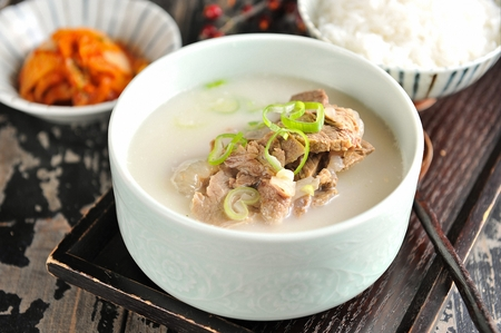 Korean cuisine Sullungtang, ox bone soup with spring onions garnish in Ttukbaegi, earthen pot served with rice and kimchi