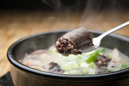 hot Sundae soup - Korean cuisine pork intestine soup with thinly sliced spring onions in Ttukbaegi, earthen pot, spoon scooping Sundae