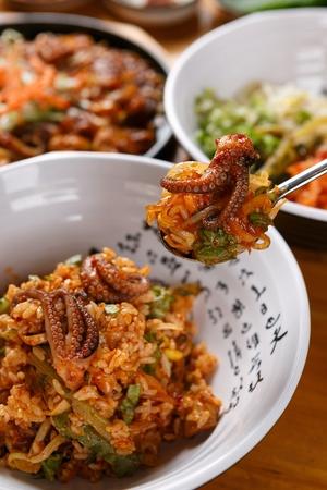 spoon scooping webfoot octopus bibimbap with various vegetables