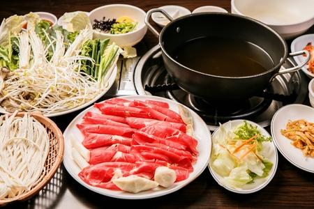 Shabu-shabu restaurant setting, beef and vegetable platters, hot pot and side dish 写真素材