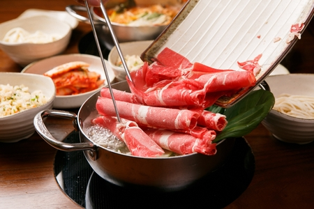 chopsticks putting beef in Shabu-shabu hot pot with bean sprouts, bok choy and vegetables in pot Stock Photo