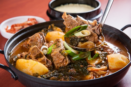 ladle scooping Korean cuisine Gamjatang, spicy pork back-bone stew with potato, mushroom and spring onion from pot