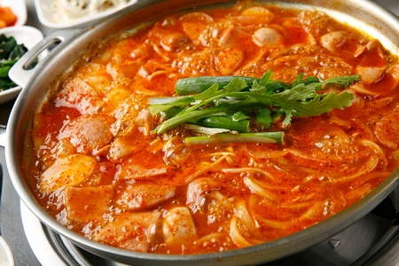 Budae jjigae, spicy sausage stew with ingredients like ham, noodles, kimchi, rice cake, kimchi and garlic chives in fry pan