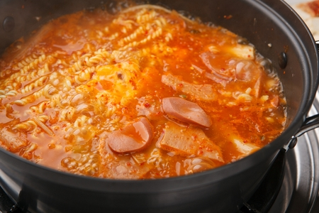 boiling Budae jjigae, spicy sausage stew with noodles,cheese, ham, pork, bean sprouts, garlic chives and onion on fry pan