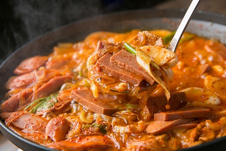 Ladle scooping boiling Budae jjigae, spicy sausage stew with ham, noodles, tofu and spring onion from fry pan
