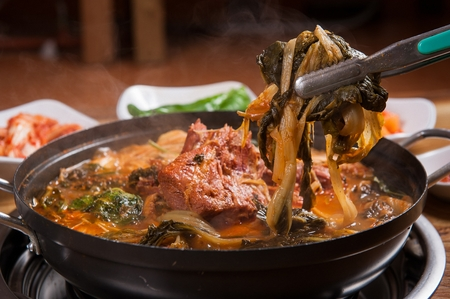 Korean cuisine Gamjatang, spicy pork back-bone stew with dried radish greens held in tongs