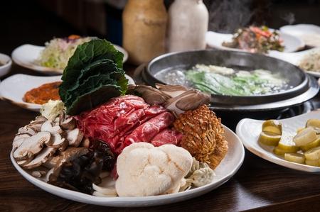 assorted mushrooms on plate, beef, dumplings and soup, ingredients of Shabu-shabu