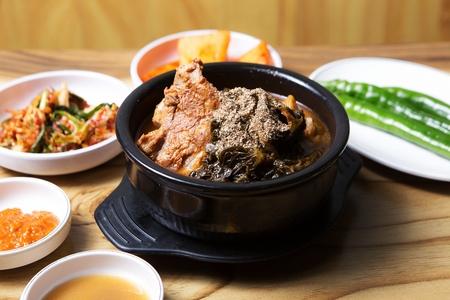Korean cuisine Gamjatang, spicy pork back-bone stew in Ttukbaegi, earthen pot served with Ban-chan side dish