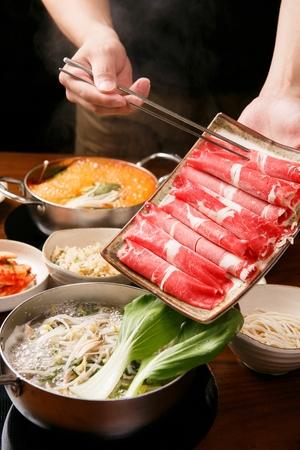 chopsticks dipping beef in Shabu-shabu hot pot with vegetables
