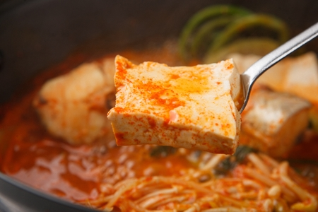 spicy codfish soup with vegetables, tofu scooped with ladle Stockfoto