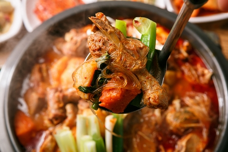 ladle scooping meat from Korean cuisine Gamjatang, spicy pork back-bone stew with spring onion, sesame leaf and mushroom from pot