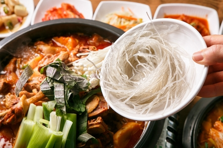 pouring noodles into Korean cuisine Gamjatang, spicy pork back-bone stew with potato with vegetables on pot 版權商用圖片