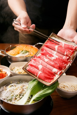 chopsticks putting beef in Shabu-shabu hot pot with bean sprouts, bok choy and vegetables in pot 写真素材