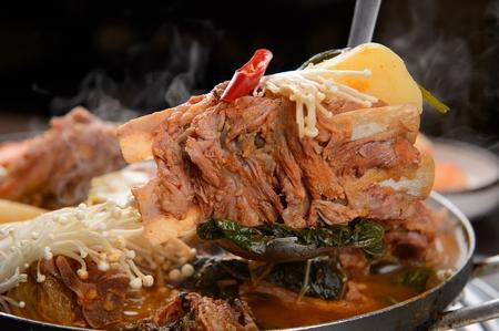 ladle scooping Korean cuisine Gamjatang, spicy pork back-bone stew with spring onion, sesame leaf, mushroom and seasoned chicken from pot 版權商用圖片