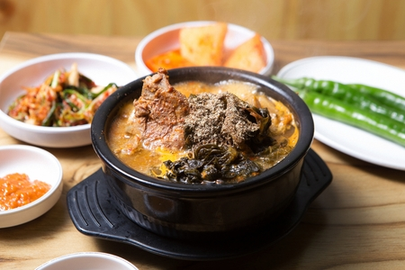 Korean cuisine Gamjatang, spicy pork back-bone stew served in Ttukbaegi, earthen pot with Korean Ban-chan, side dish 版權商用圖片