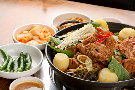 Korean cuisine Gamjatang, spicy pork back-bone stew with potato, mushroom and spring onion in pot